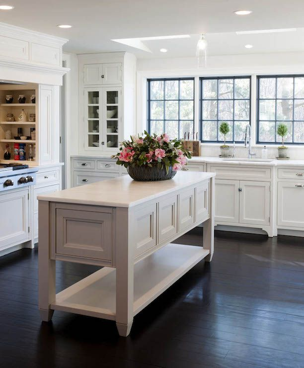 Beautiful kitchen features a light gray freestanding island with shelf topped with a honed white marble counter over espresso hardwood floors.