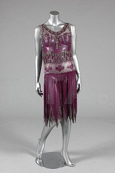A beaded magenta chiffon flapper dress, circa 1926, adorned with clear bugle beads and rhinestones, the bodice with winged griffin-like creatures, quatrefoils to the waisband, fleur de lys to the skirt, and dense beading to the van-dyke hem. Via Kerry Taylor Auctions.