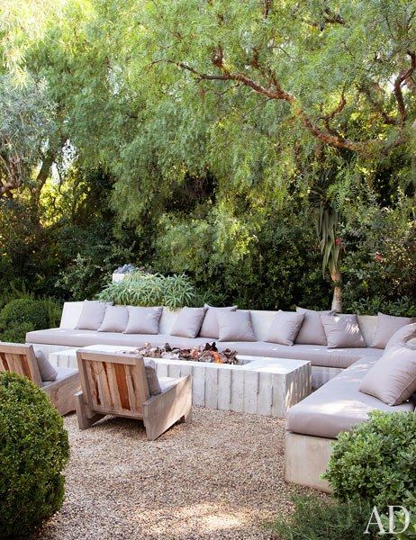 A cushioned concrete seating area with a fire pit offers a cozy spot for relaxing outdoors | archdigest.com