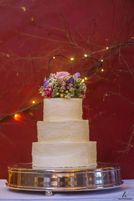 Wedding cake decorated with a mixture of fresh flowers. Jimazen Flowers.