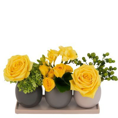 Grace - A rhythmic design in three ceramic vases on a tray. The flowers include roses, freesia, hypericum and hydrangea.