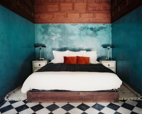 Grande sophistication des couleurs et de la décoration qui reste pourtant chaleureuse. Plafond en bois ancien, carrelage damier noir et blanc, magnifique traitement du mur avec un bleu nuancé, traité comme un ciel nuageux, qui contraste avec le rouge, le blanc et le noir du linge de lit.