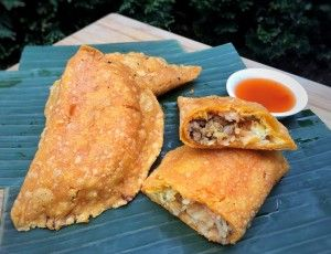 """""""EMPANADA""""  Another delicacy from the Ilocos Norte province would be the empanada, the orang coating is made from Mochiko Rice flour and orange food coloring. And there are different types of Empanada, the ordinary and the special empanada, the difference are the fillings. Ordinary empanada only have the grated unripe green papaya, sauteed mung beans, garlic and egg, while the special has """"Longanisa"""" (sausage) added besides the fillings from the ordinary empanada."""