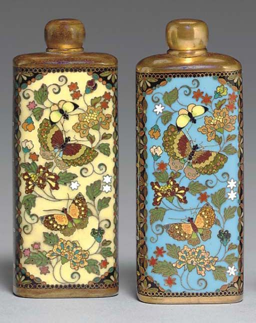Two Cloisonné Enamel Scent Bottles Meiji period (19th century), signed Kyoto Namikawa [workshop of Namikawa Yasuyuki, 1845-1927] Each bottle enamelled with two panels of butterflies and scrolling vines and flowers against a blue or yellow ground worked in gilt wires, the surrounding areas with floret lozenges on a black ground; mounts brass 3¼in. (8.3cm.) high each (2)