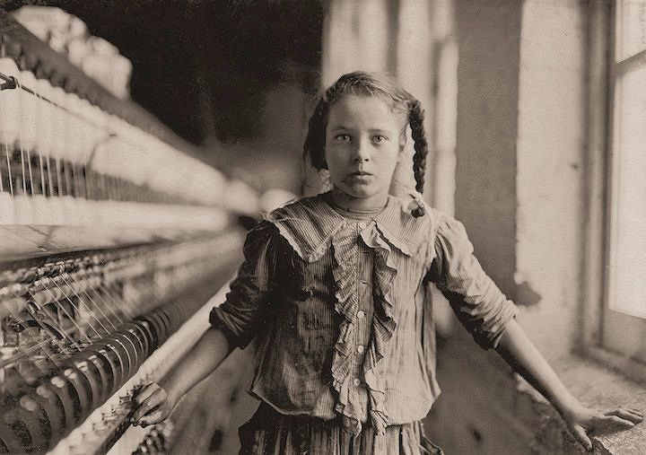"Amazing collection of child labour portraits: one of the spinners in Whitnel Cotton Mill. She was 51 inches high. Has been in the mill one year. Sometimes works at night. Runs 4 sides - 48 cents a day. When asked how old she was, she hesitated, then said, ""I don't remember,"" then added confidentially, ""I'm not old enough to work, but do just the same."" Out of 50 employees, there were ten children about her size. Whitnel, North Carolina."