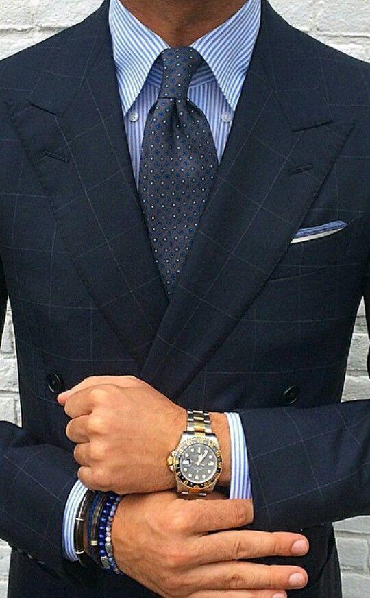 Acheter la tenue sur Lookastic:  https://lookastic.fr/mode-homme/tenues/blazer-croise-chemise-de-ville-cravate--montre-bracelet/10785  — Chemise de ville à rayures verticales blanc et bleu  — Cravate á pois gris foncé  — Pochette de costume blanc et bleu  — Blazer croisé à carreaux bleu marine  — Montre argenté  — Bracelet bleu marine