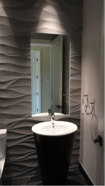 This powder room makes use of a hand carved Italian sandstone for a strong statement on the wall and black slate on the floor.
