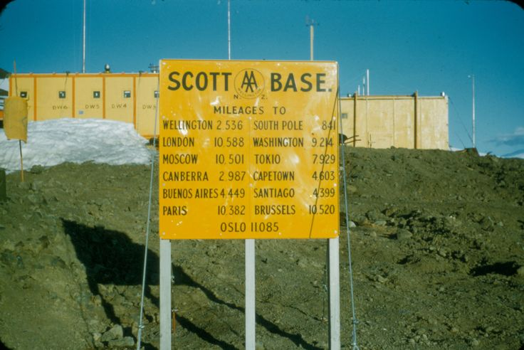 Automobile Association sign at Scott Base, showing distance to various places around the world. Taken by Alun Breese whilst serving on RNZAF Antarctic Flight, Tran-Antarctic Expedition, October '57 - Feb '58. From the collection of the Air Force Museum of New Zealand.