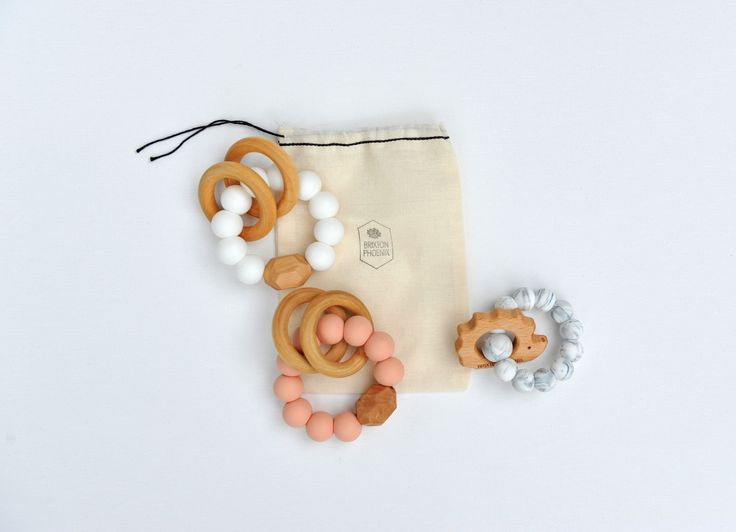 Rattle Teether - Dusty Rose  $18.00  This dusty rose rattle teether by Brixton Phoenix is a must have for the tiny princess in your life!  Made with very strong nylon cord specially knotted and strength tested to avoid breakage. Each teether comes complete in a muslin bag and includes safety and maintenance suggestions.   100% Food Grade Silicone 100% Non Toxic BPA Free
