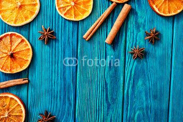 blue wooden background with orange , cinnamon and spices
