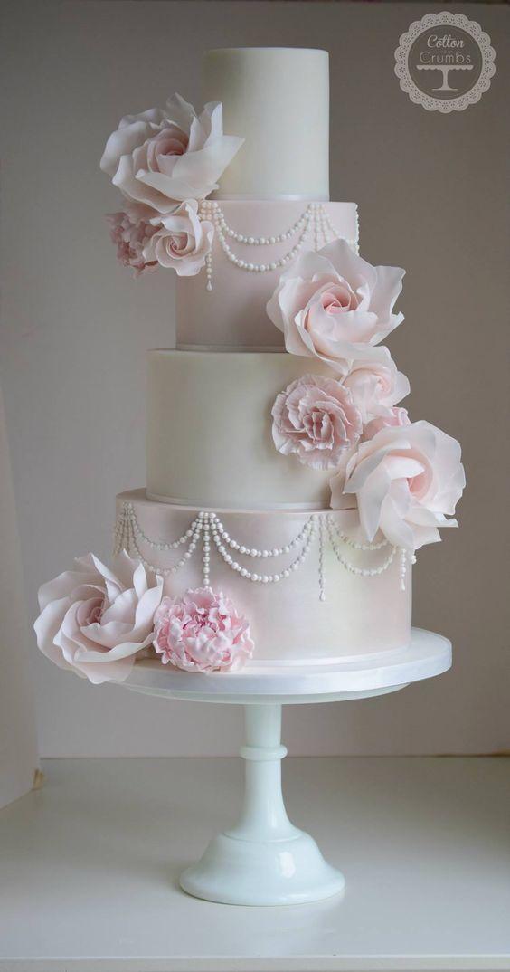 Hoch entwickelte vierreihige weiße und rosa Hochzeitstorte mit perlenbesetzten Details; …   – Wedding Cakes