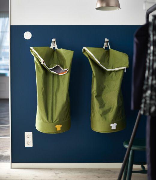 KLEUR NACHTBLAUW & MOSGROEN -  Twee groene IKEA HUMLARE zakken met was hangen aan een blauwe wand