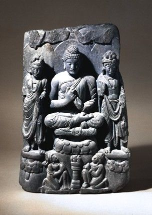 Panel showing the Buddha preaching between two standing Bodhisattvas. The haloed and seated Buddha wears the over-robe leaving his right shoulder and feet bare and an undergarment visible below his right shoulder; it lies on the seat beside a fall of gathered drapery from his left wrist which spreads out. The drapery folds are defined mainly by paired grooves separating broad flat strips. The head is a long and regular oval; the hair, representing the Indian snail-shell curl tradition…