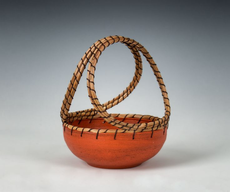 Orange Basket by Hannie Goldgewicht. An inspired pairing of ceramics and basketry results in an exquisite and charming little wheel-thrown vessel. Its richly hued body with woven pine needle edges and handle draws the eye and hand. Each is unique and will vary.