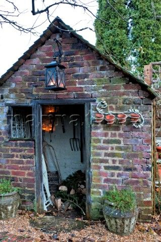 Lit lantern on brick wood shed in Walberton West Sussex England UK