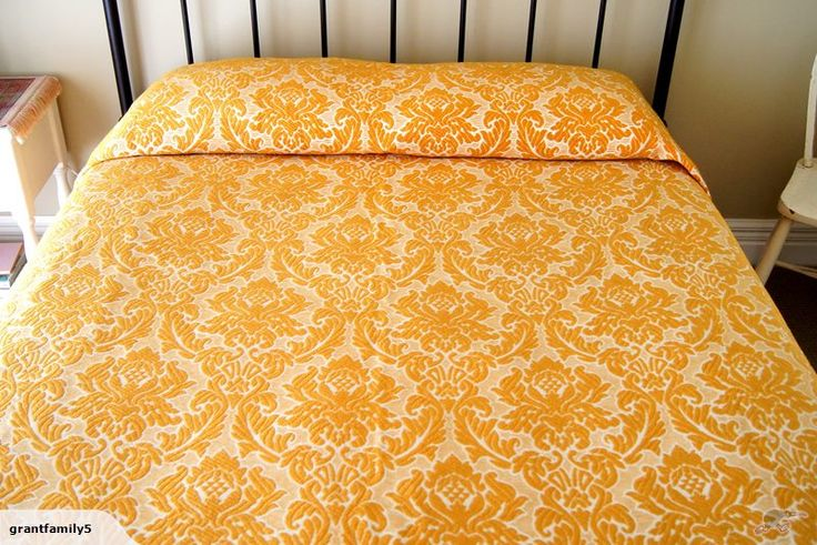 Luxurious, golden-coloured brocade bedspread featuring an ornate pattern on a creamy-white background with deep fringe. Vintage.
