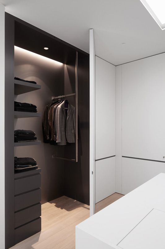 concealed wardrobe with rich brown interior against the clean contemporary white . Designed by Belgian office Minus.