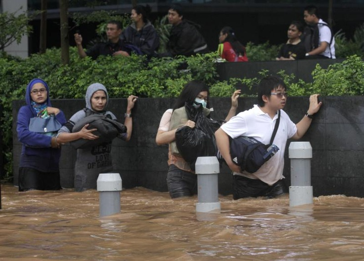 Workers cross a flooded area at the business district in Jakarta on January 17, 2013 | © Supri | Reuters