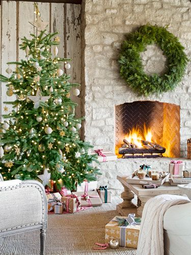 A stone fireplace keeps an elegant Christmas tree toasty on the covered