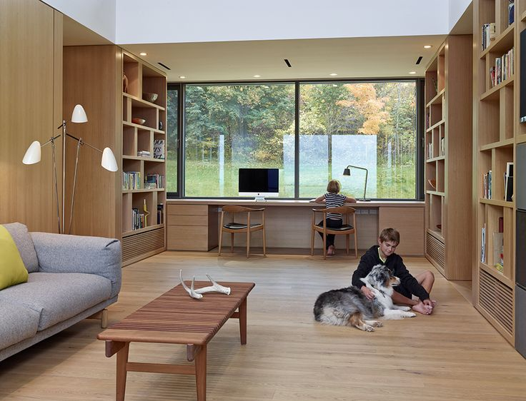 The lower submerged level is comprised of the kids' and guest bedrooms as well as the multi-purpose room—is a popular hangout for the kids and family dog, Roxy. The Chair and Bar Bench, both by Hans Wegner for PP Møbler, a Muuto 3-seater sofa by Andersen & Voll, and David Weeks' Tripod No. 303 floor lamp mix midcentury modern with contemporary design.