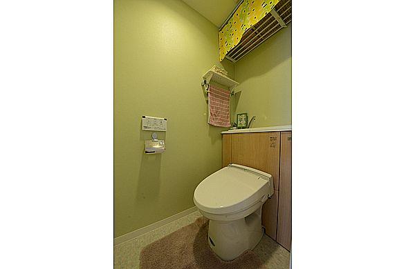 トイレは収納付きのスッキリ見えるタイプへ交換。壁の色はグリーンで個性的に。