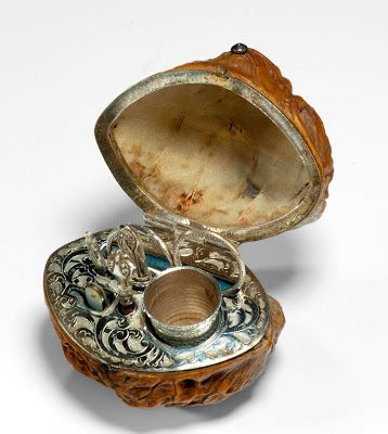 A tiny étui encased in a walnut with silver metal fittings. Includes scissors, thimble, needle, pin case, and stiletto.