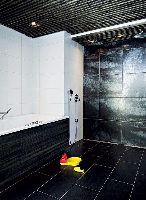 Suuret ja kiiltävät laatat luovat amme- ja suihkutilaan selkeät linjat. Puusepän tekemät reunat ja kattopaneelit ovat kuultoöljyttyä puuta. Suihkutilan metallisävyinen laatta luo upean kontrastin valkoisen seinän ja tumman katon kanssa. Lattiakaivoina käytettiin Unidrainin pitkulaisia suihkukaivoja, jotka mahdollistivat isojen lattialaattojen käytön. Hansgrohen hanat ja suihkut hankittiin Kylpystudiosta. | Kaupunkilainen savusauna | Koti ja keittiö