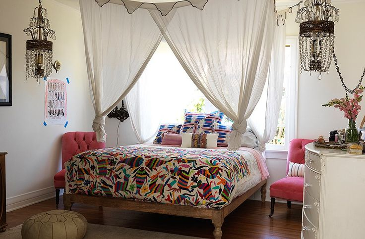 Rounding out the global-glam look are pink velvet chairs, a colorful Mexican blanket, and a set of chandeliers, beneath a gauzy white DIY bed canopy.