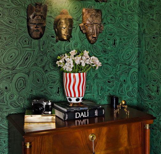 Destaca el color verde y diseño de piedra del papel mural, en el que colgamos unas máscaras africanas doradas. Sobre la cómoda inglesa de madera de nogal dispusimos un florero con orquídeas que contrastara con el color del muro. En éste .