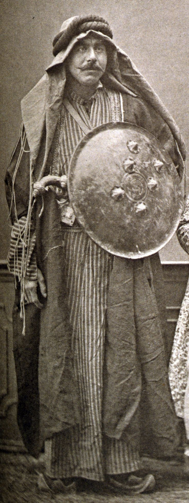 "Ottoman Arab of the Chammar (Shammar) tribe, he has a pistol (kuber) and a kalkan shield made from lacquerd hardened leather with six bosses. From:Les costumes populaires de la Turquie en 1873, 74 photographic plates by Pascal Sebah, published by the Imperial Ottoman Commission for the ""Exposition Universelle"" of Vienna in 1873."