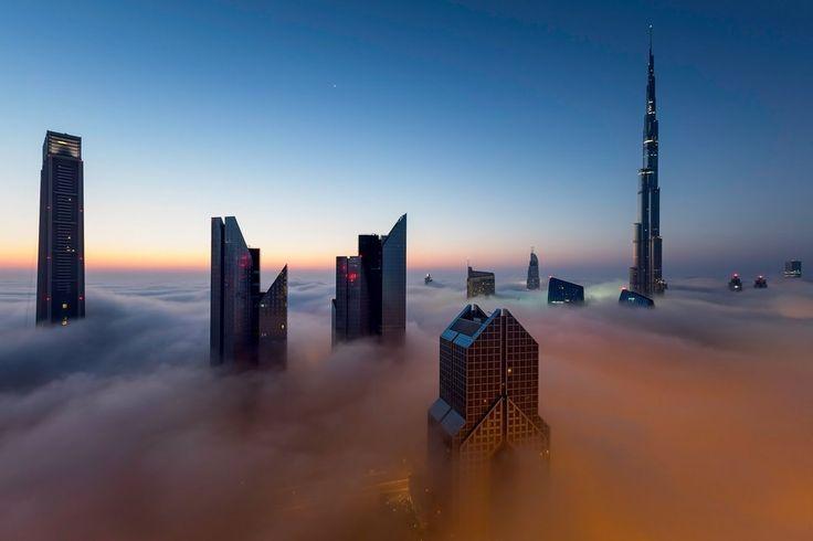 Os mais altos edifícios de Dubai perfuram um denso manto de neblina que encobria a cidade pouco antes do nascer do sol
