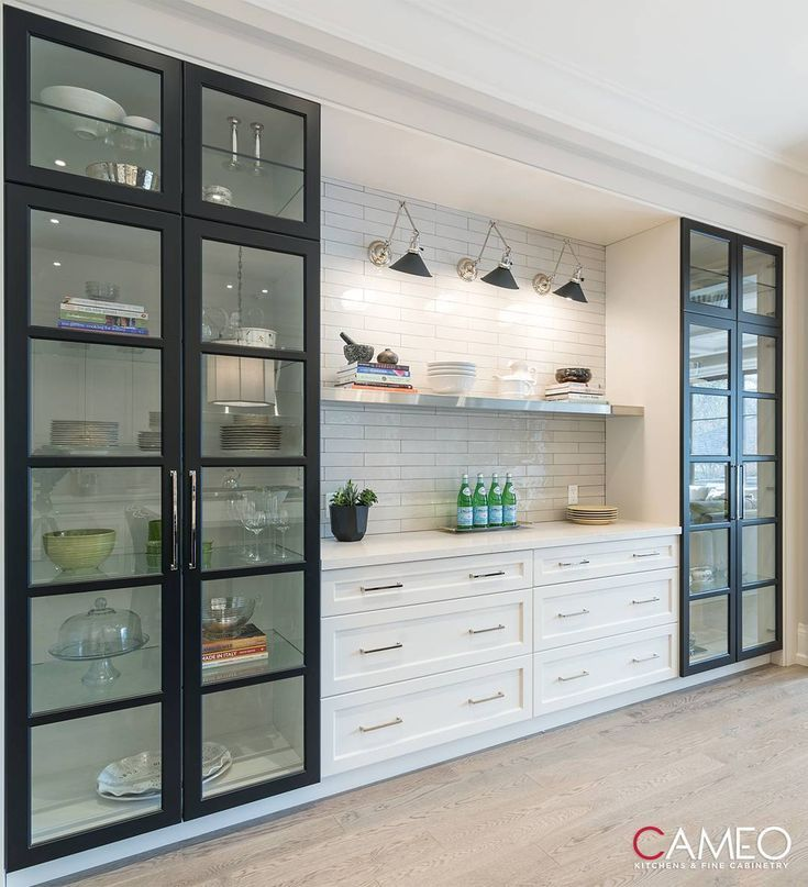 modern kitchen with white cabinets and open glass …