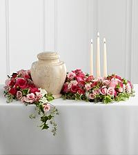 A sophisticated way to display their urn at their final farewell service. Fuchsia and pale pink roses and spray roses are accented with lush greens to form an exquisite arrangement that winds around the base of the urn and curls around 3 ivory taper candles, creating a warm and comforting presentation that commemorates a life that brought kindness and beauty into the lives of others. Approximately 27-inches in length.