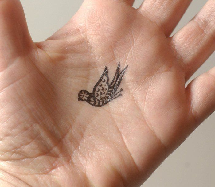 A tiny tattoo of a paisley bird in the palm of the hand. Small tattoos like this aren't as visible as a large, full palm tattoo.