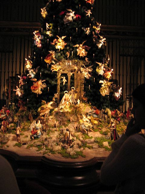 The tree has hundreds of angels descending upon Baby Jesus, while shepards are climbing the rough terrain to go worship him. The manger is set at the base of the tree.