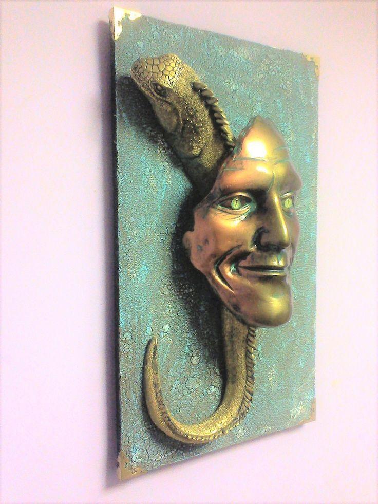 Маска Интерьерная Внутренняя этергия и Психическая сила  .Скульптурная композиция: символ внутренней силы и психической энергии- улыбающееся лицо с игуаной. Глаза лица-это нарисованные зрачки животного в линзах. Все элементы работы вылиты из скульптурного гипса, прикреплены к стенду с помощью болтов, вформованных в заготовки, проклеены и покрыты лаком. По углам декоративного стенда прибиты металлические уголки, работа вешается на стену с помощью мебельного подвеса.