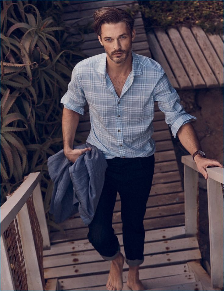 Model Ben Hill wears a J.Hilburn soft wash heather blue shirt with J Brand denim jeans in black.