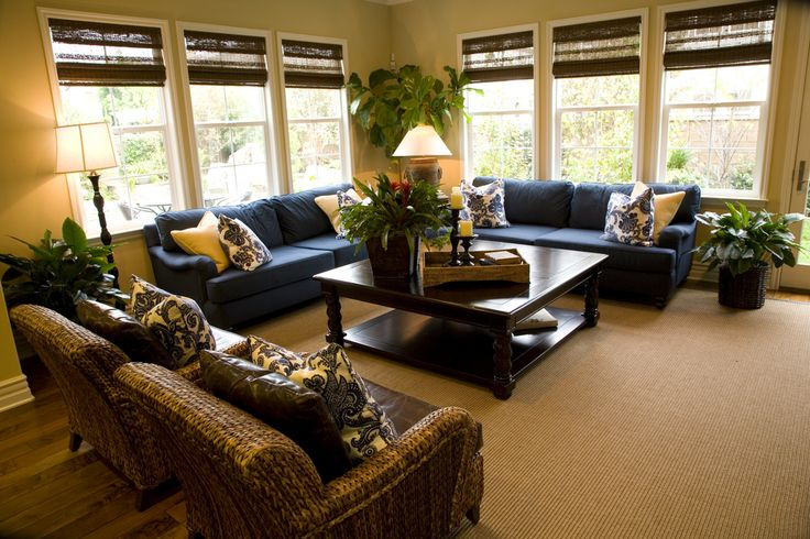 This living room space is flooded with natural light, highlighting wicker and leather chairs, blue twin couches and large dark wood coffee table.