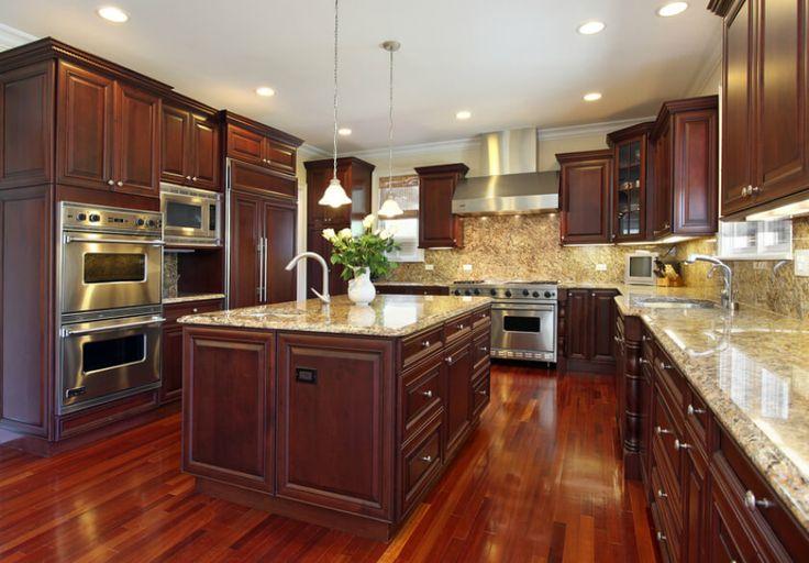 Esta cocina de gran lujo alarde rica madera de cerezo de suelo a techo, con gabinetes adornado por todas partes.  encimeras de granito de color beige añaden un toque de contraste y brillo, que continúa en la superficie de la isla.  Con un lavabo y matriz integrada de cajones de almacenamiento, la isla es un centro altamente funcional de esta cocina.
