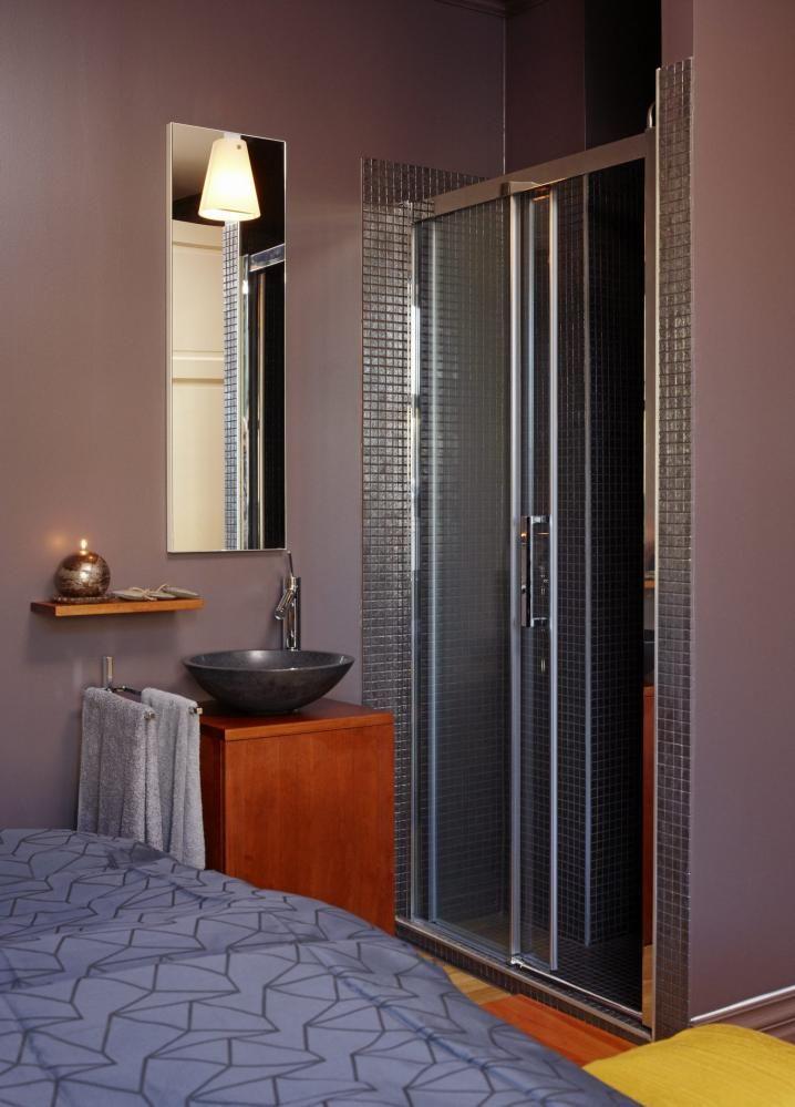 MØRK HARMONI: Gjesteværelset gir en følelse av å være på hotell, med dusjsone som en del av rommet. Dusjen og vasken er plassert i et hjørne. Fargenpå flisene fra Bisazza harmonerer med veggen. Kranen er fra Hansgrohe. Den mørke marmorvasken er fra Korsbakken.