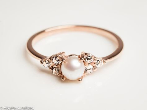A dainty rose gold pearl engagement ring with real diamonds. Express your unique and elegant style with your engagement ring choice ♡ ► FEATURES; Gemstones: Freshwater Pearl: 3mm Diamond: 6*2mm Total diamond carat weight: 0.18 (Color G; clarity VS) Material Options: 14k Rose Gold, 14k Yellow Gold, 14k White Gold Size: All ring sizes ara available ► HOW TO ORDER; Please select your preffered size and material from the menu while adding to card. ► PROCESSING & SHIPPING ❥Your order will be h...