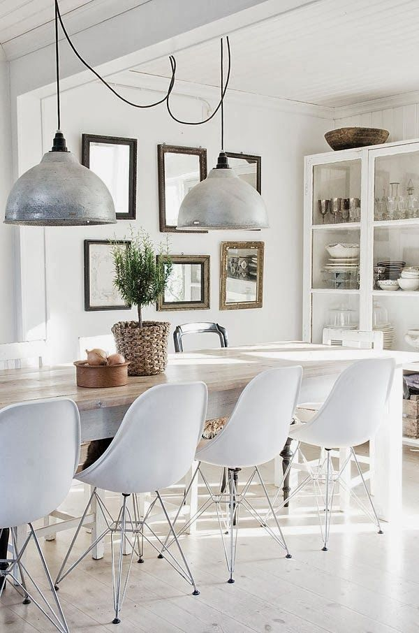 White dining room with Eames chairs and a long table. Also like the different mirrors on the wall...