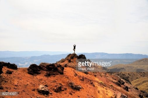Stock Photo : Man in yoga tree pose on rock out cropping.