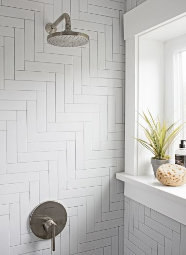 Amazing And White Bathroom Features Walls Clad In A White Herringbone Tiles