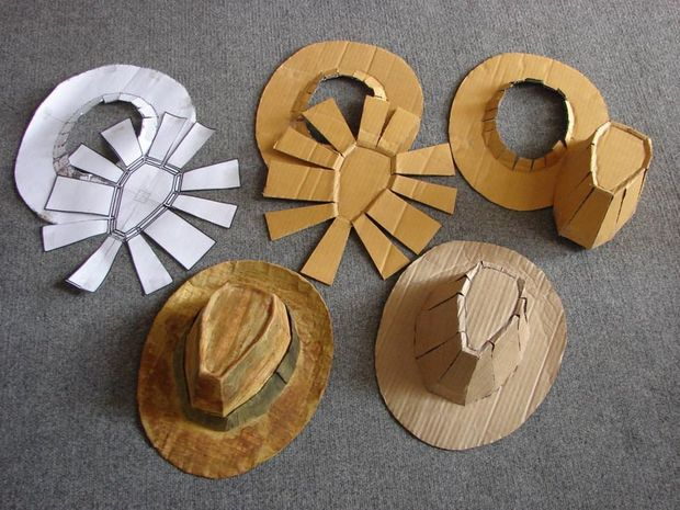 Make a cardboard Fedora...miniaturize for doll sizes.  Good to know for craft projects.