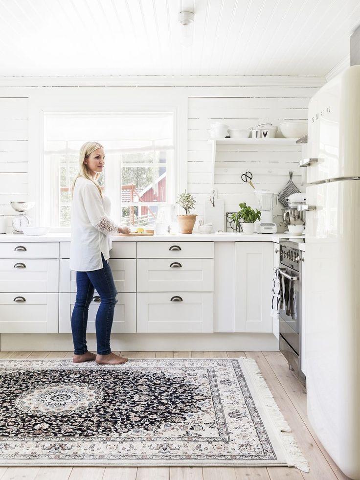 Efter många timmars skissande kom hon och Peter fram till att de kunde använda det dåvarande vardagsrummet som matsal och bygga till en del där ett nytt vardagsrum kunde få plats. Maria gillar enkelhet i inredningen. I köket skippade hon överskåp för att få en luftig känsla. Väggarna klädda med vitmålad råspont ger rummet en lantlig karaktär. Köksskåp, Ikea. Matta, Rugvista. Lerkruka från Hjärtats rum i Dala-Järna. Spis och kyl, Smeg.