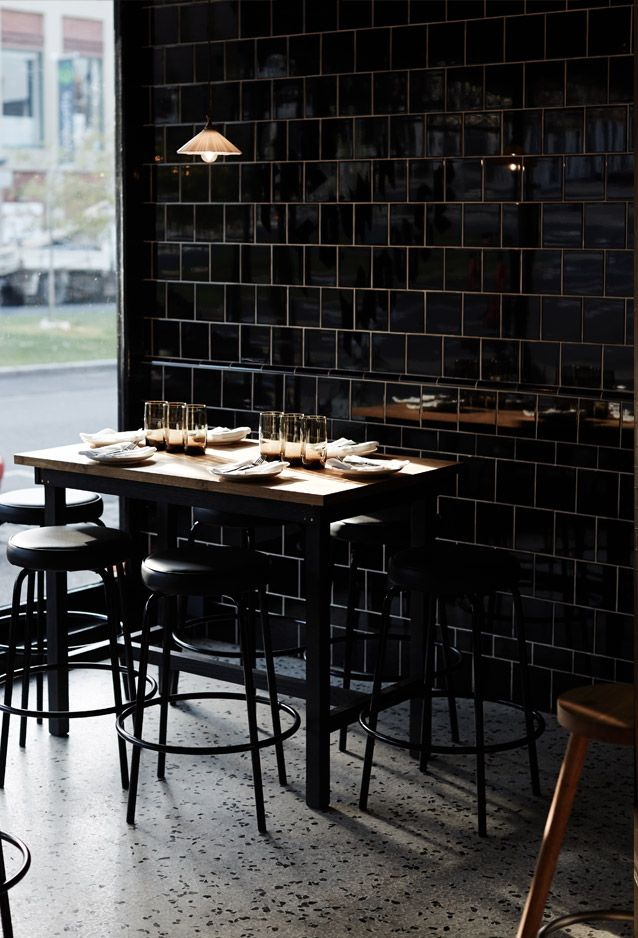 Town Mouse in Melbourne's Drummond Street | deco combination of reflective black tiles over white grout with green borders, these are balanced by the polished, aggregate-flecked concrete floors. Further touches like the retro pendant lighting hanging throughout, almost bench-height seating, custom American oak tables and gilded gold leaf on the windows help soften the mood