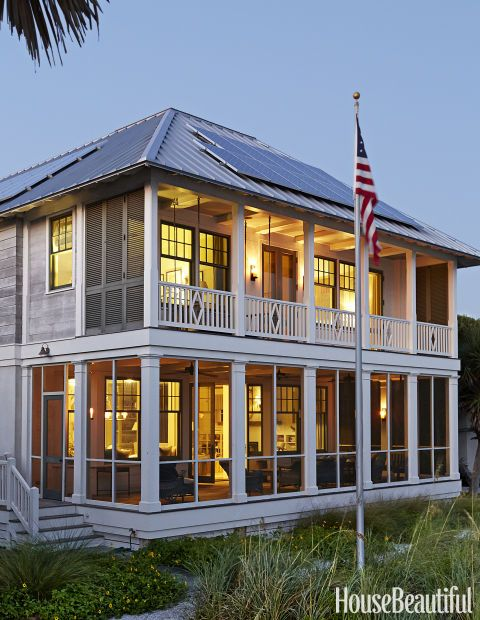 "Near Seaside, Florida, a two-story beach-front cottage designed by Birmingham, Alabama-based architect James F. Carter features an old-fashioned tin roof and traditional stacked screened porches. ""It has the echo of a friendlier time,"" says Carter, but also solar panels and eco-conscious materials. Click through for beautiful house exterior design ideas."