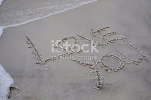 The words LOVE YOU written in sand at the beach