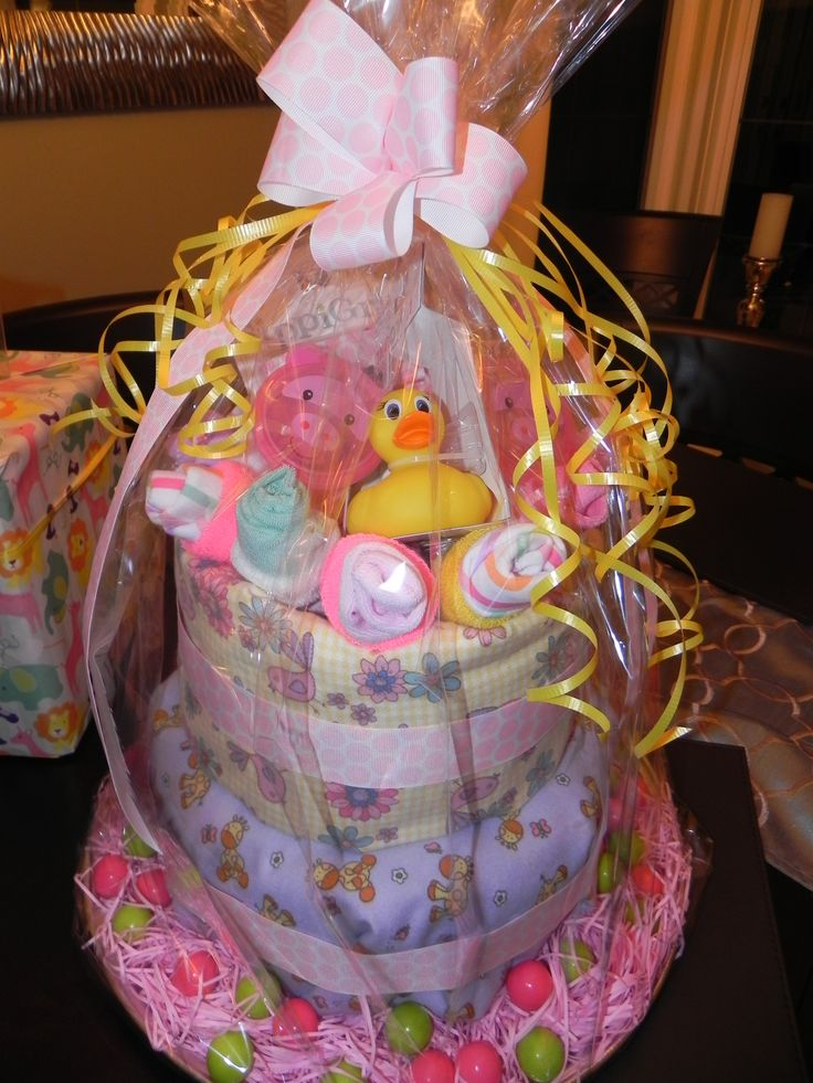 Baby Shower 2 tier 'cake' made with disposable diapers wrapped in receiving blankets/ribbon & embellishments. Colourful gumballs and pink grass decorate the bottom while baby sock & rolled up infant facecloth 'Ice Cream Cone' decorate the top. - Carolyn Cowan Interiors